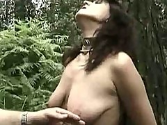 Hot milf slave tied to a tree got pulled on her nipples and