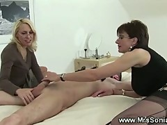 Mistresses stroking slaves hard cock