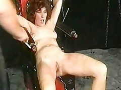 Two masked masters in a dungeon spank milf slave tied to a c