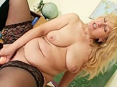 Mature blonde teacher with huge tits inserting an toy in the classroom
